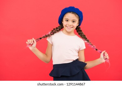 Kid little cute fashion girl posing with long braids and hat red background. Fashion girl. Fashionable beret accessory. Teenage fashion. French fashion attribute. Child small girl happy smiling baby.