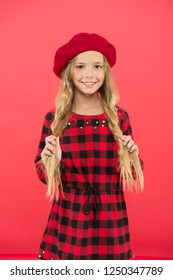 Kid little cute girl with long blonde hair posing in beret hat and checkered dress red background. Beret style inspiration. Fashionable beret accessory for female. Wear beret like fashion girl.