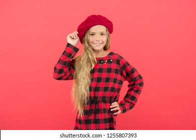 Kid little cute girl with long blonde hair posing in beret hat and checkered dress red background. Fashionable beret accessory for female. Beret style inspiration. Wear beret like fashion girl.