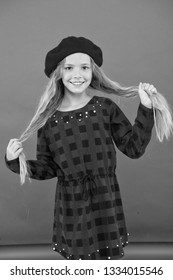 Kid little cute girl with long hair posing in hat red background. How to wear french beret. Beret style inspiration. Fashionable beret accessory for female. How to wear beret like fashion girl.