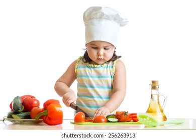 kid little girl helping at kitchen with salad making
