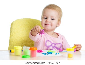 Kid little girl learning to use colorful play dough isolated on white background