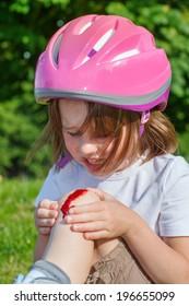 Kid looking at the bleeding knee