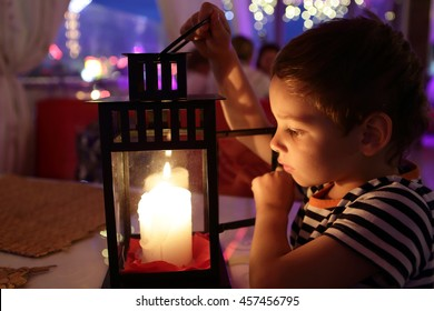 Kid looking at candle in a cafe