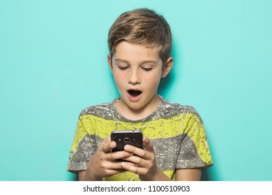 Kid looking at a cell phone with a surprised look on his face. Boy looking at his cell phone