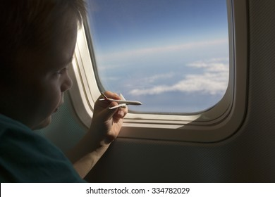 Kid looking at the clouds from an airplane. Going places, exploring the world, dreaming concept photo.