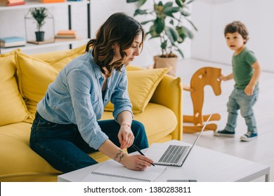 kid looking how mother working with laptop in living room