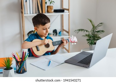 Kid looking online video lesson about soprano ukulele via laptop. Elementary school boy learning play guitar at leisure. Concept of early childhood education, e-learning, talent and music hobby