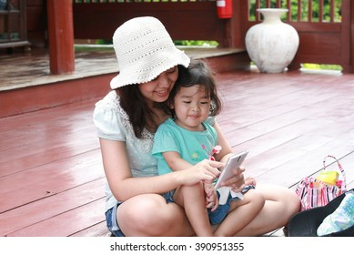 Kid looking and playing mobile phone with her mom on vacation time