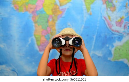 Kid is looking through binoculars around. Adventure and travel concept. Joyful background. Child is playing in his room in front of a map of the world.