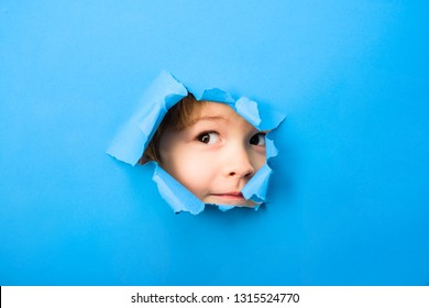 Kid looking through paper. Spy eye watching through hole. Child's eye looking through hole. Boy breaks paper. Through paper. Sale. Discount.