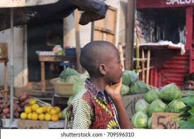 A kid looking at the vegetable and fruit market while walking in the street at the outskirts of Kinshasa, Democratic Republic of Congo. July 2015