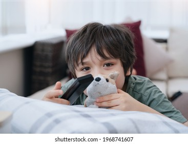 Kid lying on sofa looking at camera with smiling face, Cute boy laying down on couch holding remote, Child watching TV relaxing at home in sunny day spring or summer, Social Distancing