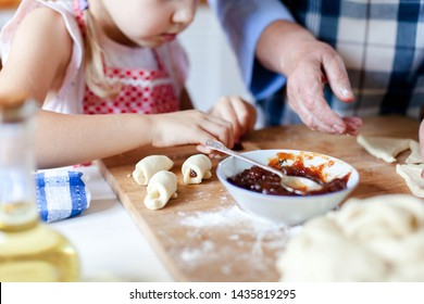 Kid makes croissants with jam. Family is cooking together at home. Dough and ingredients are on kitchen table. Grandmother and child prepare pastries. Children chef concept.