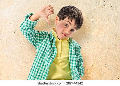 Kid making bad sign over textured background