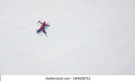 Kid making a snow angel. High point of view. Overhead view