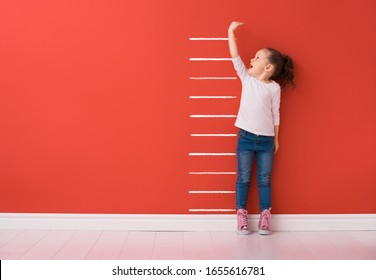 Kid is measuring the growth on the background of bright color wall. Girl power concept.
