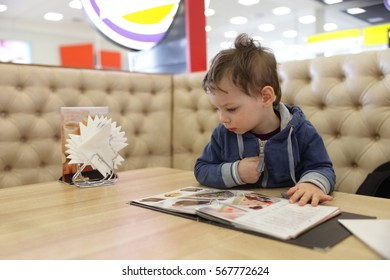 Kid with menu at the table in a cafe