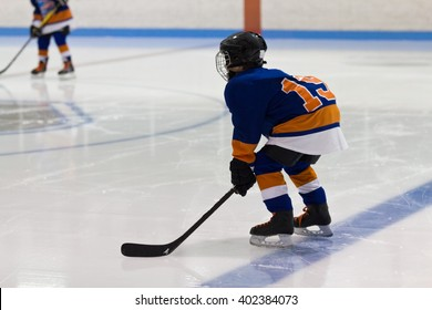 Kid minor ice hockey player gets ready for a face-off