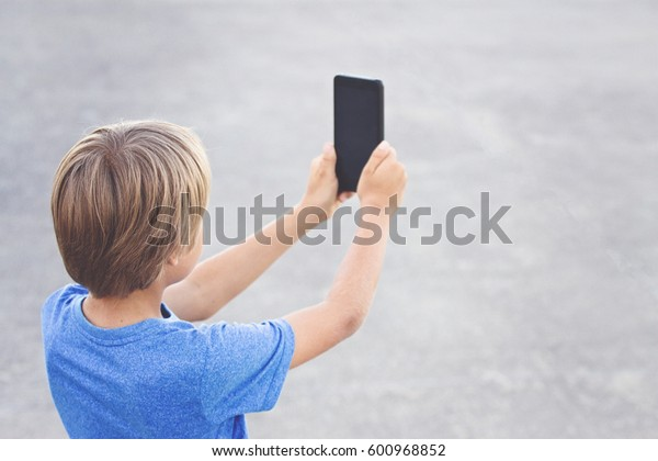 Kid with mobile phone in the street. School, people, technology, leisure concept