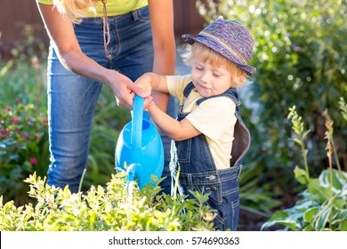 Kid with mom in garden. Child watering flowers. Mother helps little son.