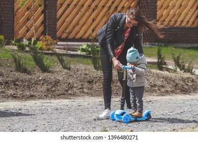 Kid and mom play outdoors with scooters. Active leisure and outdoor sport for child.