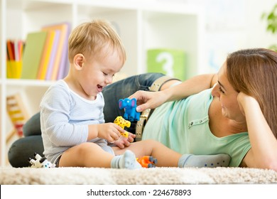kid and mom playing with toy animals indoors