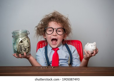 Kid and money. Funny excited child plays with money. Education for little businessman how to be rich when grow up. Student in glasses and tie with piggy bank and jar full of money