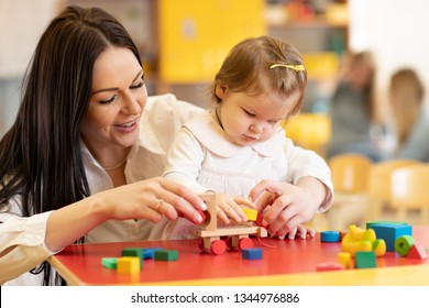 Kid with mother play with colorful wooden block toys on table in nursery