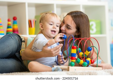 kid and mother play with educational toy indoor
