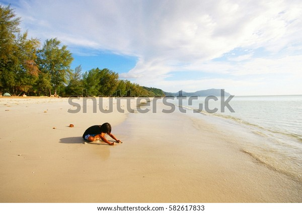 Kid on the beach playing sand