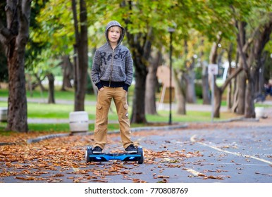 Kid on hover board in the autumn park