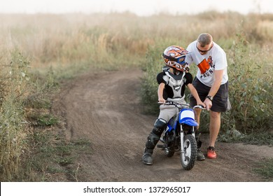Kid on a motorcycle doing motocross. A little boy learns to ride a motorbike. The coach teaches the child to drive a motorcycle. Son and father on the track.