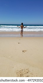 Kid with open arms alone at the Beach