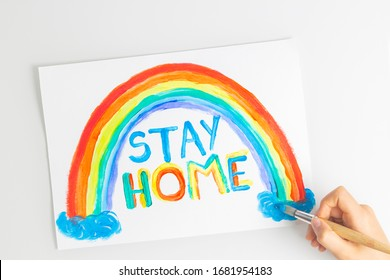 Kid painting during quarantine at home. Rainbow with words Stay at home. Social media campaign for coronavirus prevention