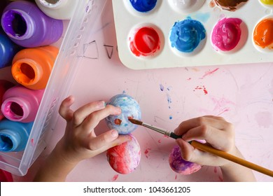 Kid painting on easter eggs. Painting is play therapy for ADHD kids (Attention deficit hyperactivity disorder),can be used to address emotional problems.