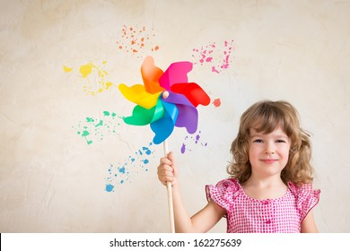 Kid painting wall with multicolor palette. Renovation concept