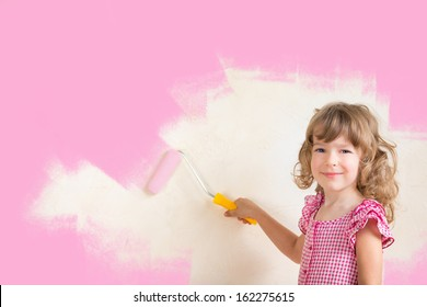 Kid painting wall with pink color. Renovation concept