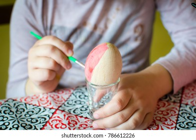 kid painting wooden egg for Easter close up with little glass as stand
