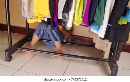 Kid play hide and seek. Hiding behind hanging clothes
