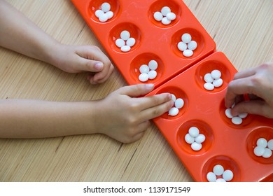 the kid play Mangala Turkish  strategy and intelligence game on the wooden table in the school.