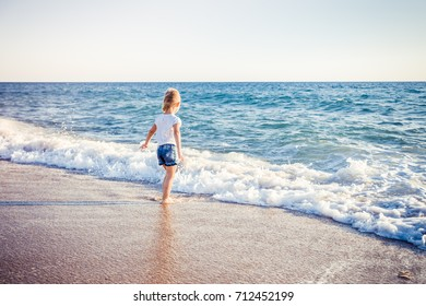 kid play with wave on summer beach