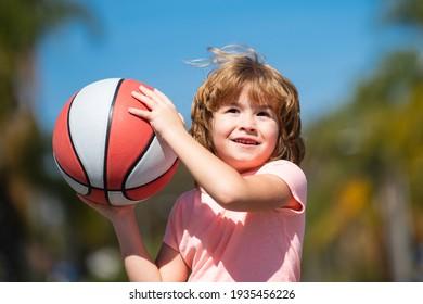 Kid playing basketball with basket ball. Child posing with a basketball ball