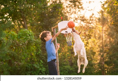 Kid playing basketball with his dog in backyard garden