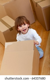 Kid playing with cardboard boxes and smiling