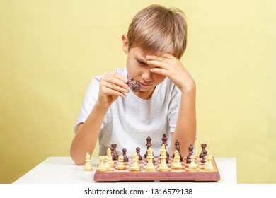 Kid playing chess. Boy looking at chess board and thinking about his strategy.