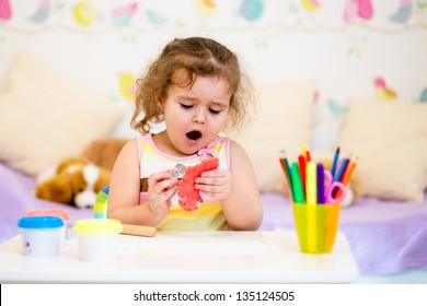 kid playing with colorful clay