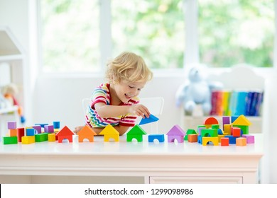 Kid playing with colorful toy blocks. Little building tower of block toys. Educational and creative toys and games for young children. Baby in white bedroom with rainbow bricks. Child at home.