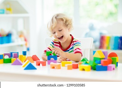 Kid playing with colorful toy blocks. Little baby building tower of block toys. Educational and creative toys and games for young children. Baby in white bedroom with rainbow bricks. Child at home.