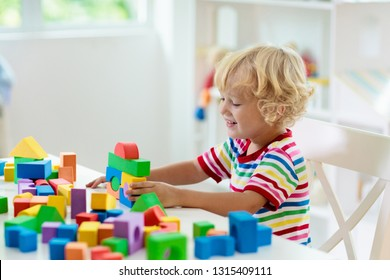 Kid playing with colorful toy blocks. Little boy building tower of block toys. Educational and creative toys and games for young children. Baby in white bedroom with rainbow bricks. Child at home.